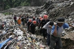 Rescue workers carry the body of a garbage scavenger who was killed in a mudslide caused by heavy rain in the city's main trash dump in Guatemala City, Friday, June 20, 2008. Six people rummaging through the trash died in the mudslide, according to authorities. (AP Photo/Moises Castillo)
